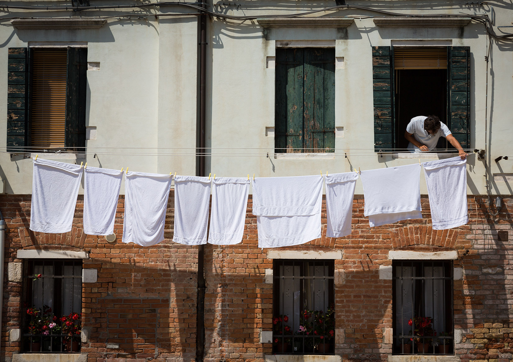Modern man laying wet clothes on a line. Venezia