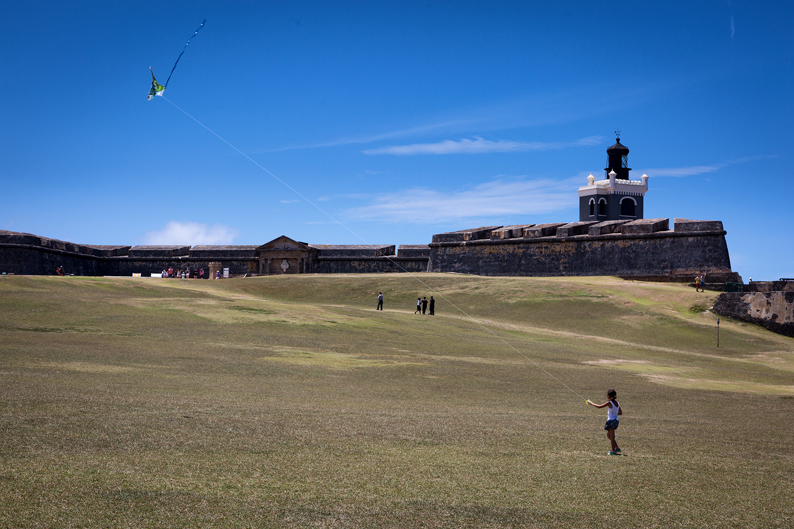 A little girl playing with a kite at El Morro in San Juan