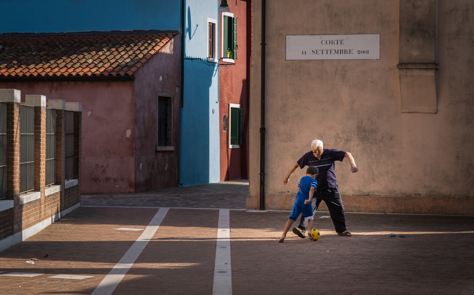 Little kid with his grandpa playing soccer in a little Venice square